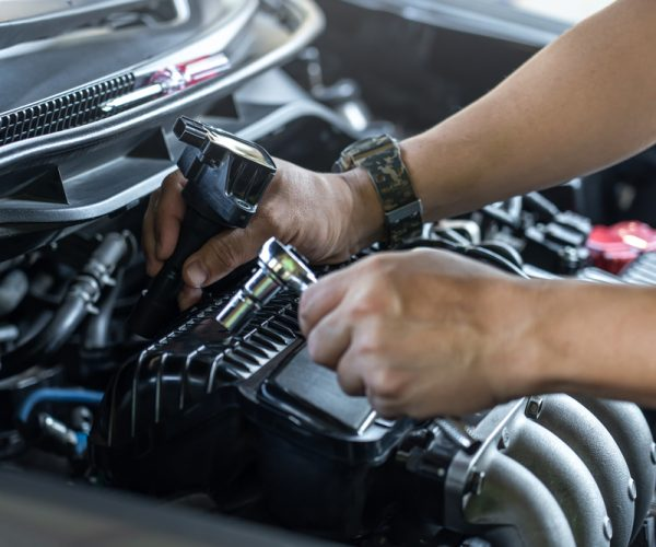 Close,Up,Spark,Plug,Coil,On,Engine,Cover,And,A